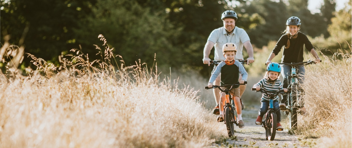Parents and their two small children ride bicycles on a path through a field of tall grass.