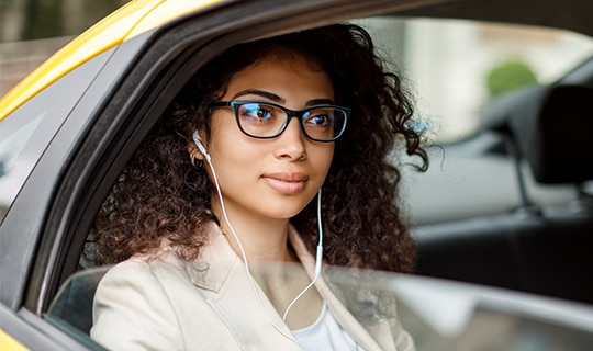 woman sitting in taxi listening to headphones