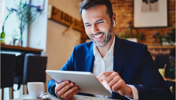 A smiling man in a suit sits at a coffee shop, working on his tablet.