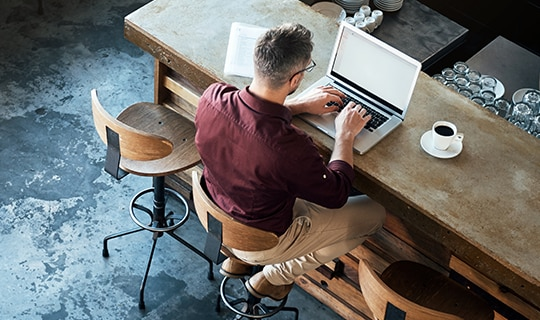 Man at desk typing on laptop