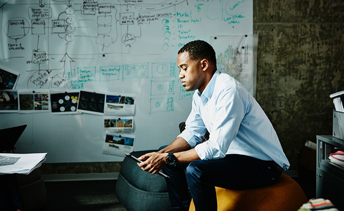 Man sitting in front of whiteboard staring down at a tablet