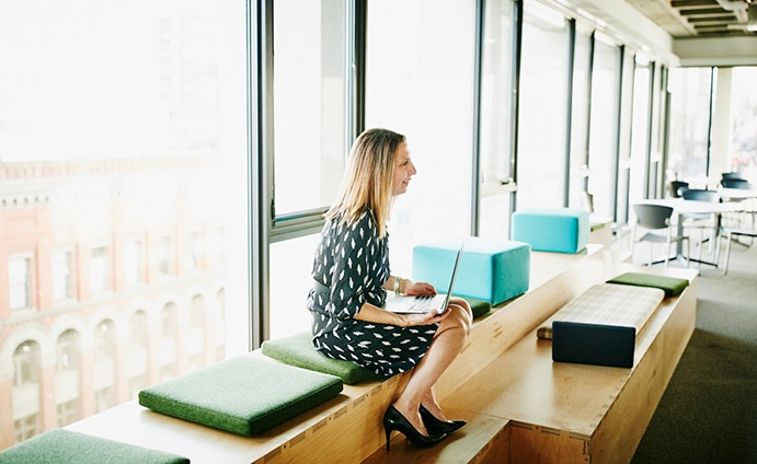 Woman sitting on bench inside with a laptop