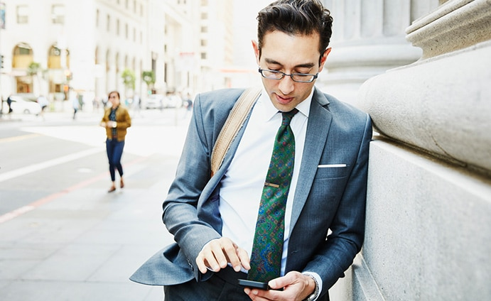 Man in business suit leaning against stone building looking at his phone