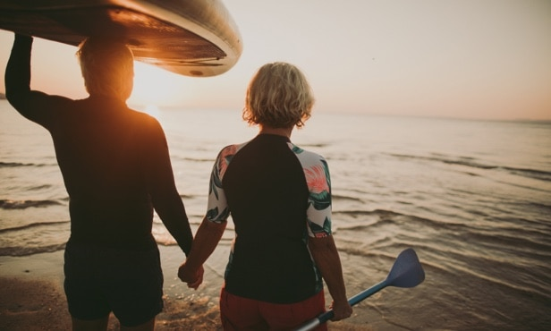Two kayakers hold hands while walking into the water at sunset.